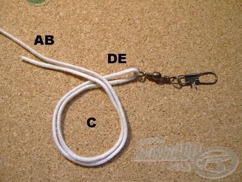 Fogjuk egymás mellé az (A) és a (B) szálat, a továbbiakban (AB)-vel jelölöm. Vegyük át az (AB) szálakat önmagukon, így megkapjuk a (C) hurkot. A metszésponttól a karabiner felé eső dupla damilrészt (DE)-vel jelölöm