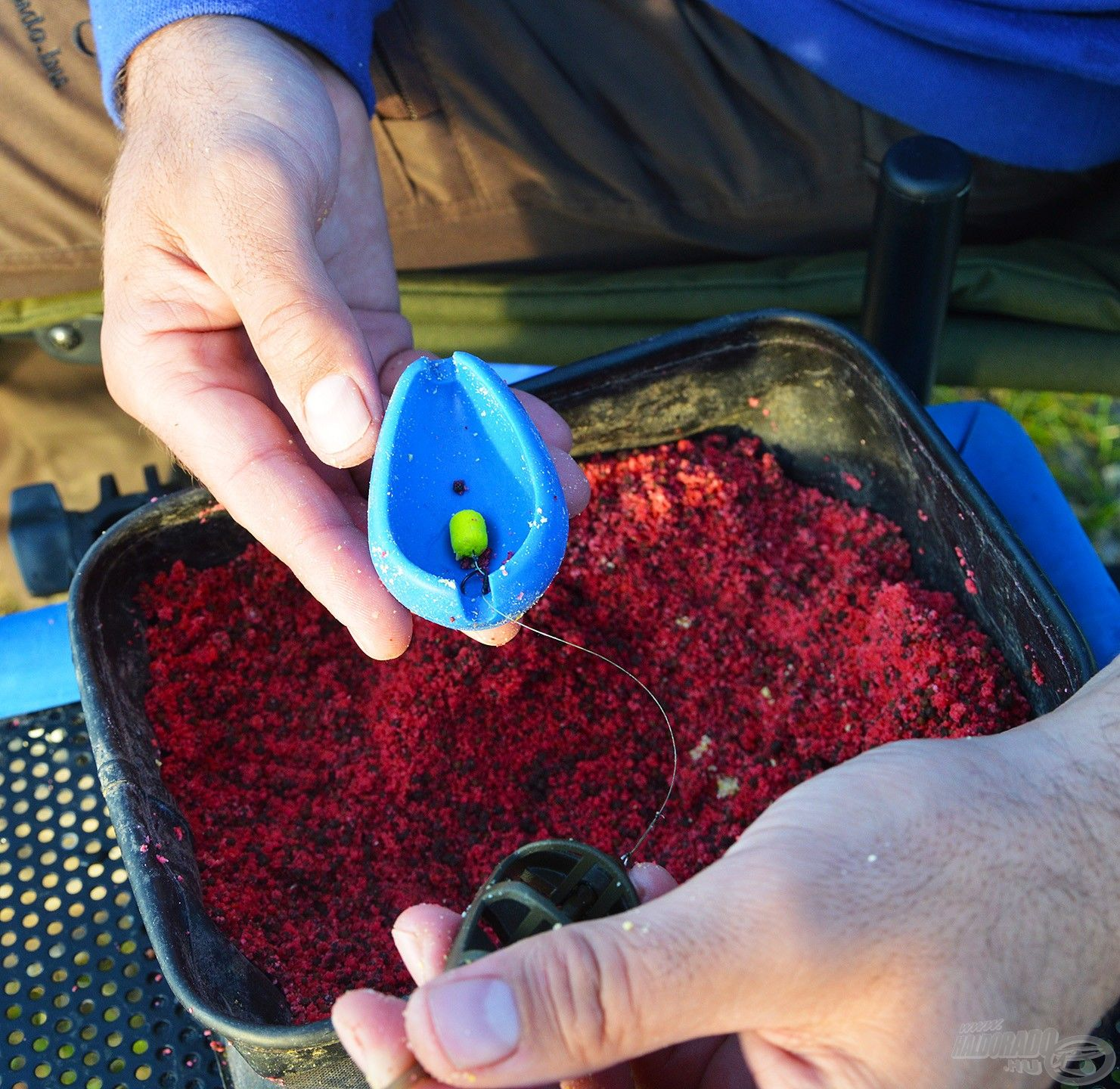 Amennyiben először a felcsalizott horgot tesszük a présbe és utána töltjük meg a kosarat, akkor a csali a gombóc tetejére kerül