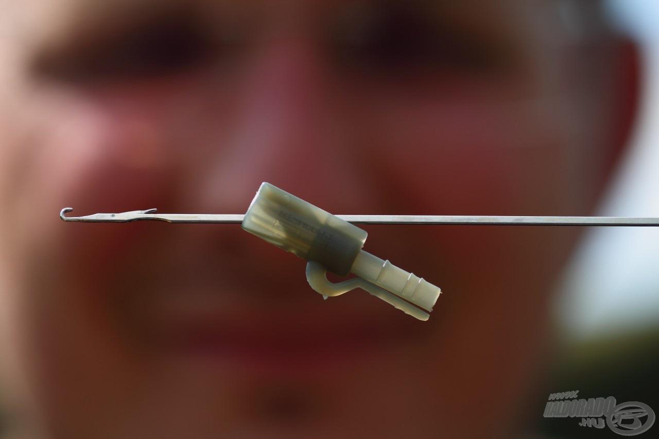 Első lépésként át kell dugni a fűzőtűt a klipsz oldalán található lyukon