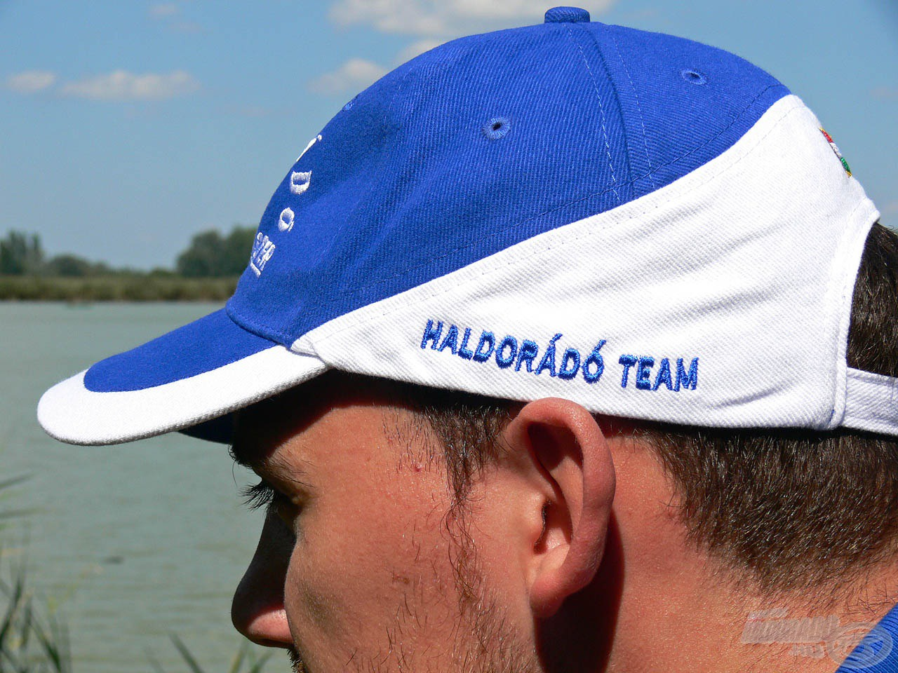 """A White&Blue sapkán az elöl lévő, nagyméretű hímzett logón kívül jobb oldalon egy igényes """"Haldorádó Team""""…"""